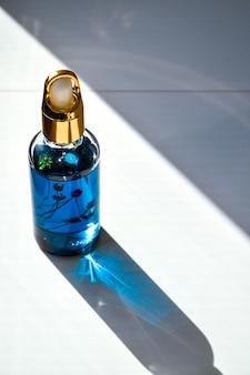 Maquette de bouteille en verre compte-gouttes. gros compte-gouttes avec de l'huile de cannabis cbd utilisée à des fins médicales. huile de cbd de marijuana sur fond blanc, ombres profondes, fleurs séchées à l'intérieur