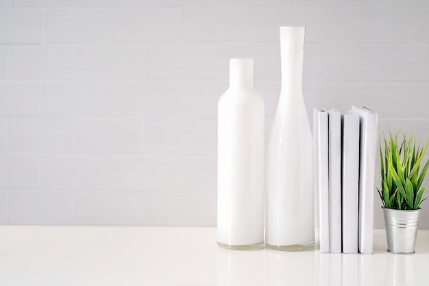 Maquette de bouteille en verre, livres et plante d'intérieur sur une table blanche avec mur de briques blanches