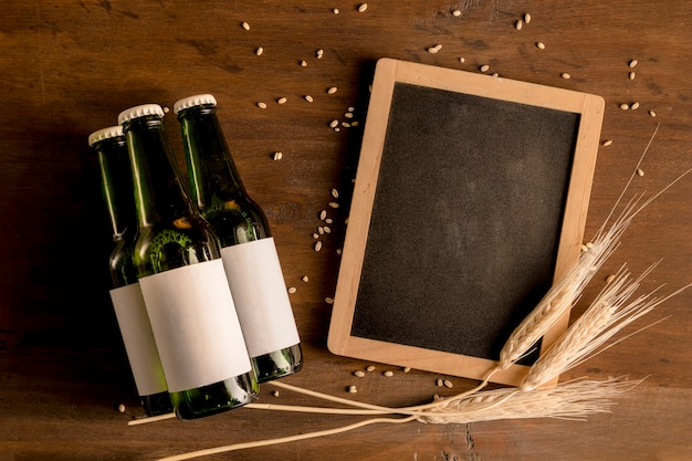 Maquette de bouteilles de bière verte avec tableau noir sur une table en bois
