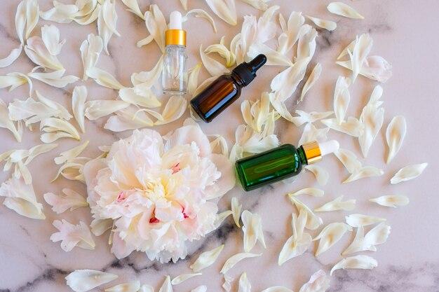 Maquette de bouteilles en verre de sérum cosmétique pour le visage avec une pipette sur un fond de marbre avec des fleurs de pivoine. concept de beauté féminine, modèle vide. espace de copie.
