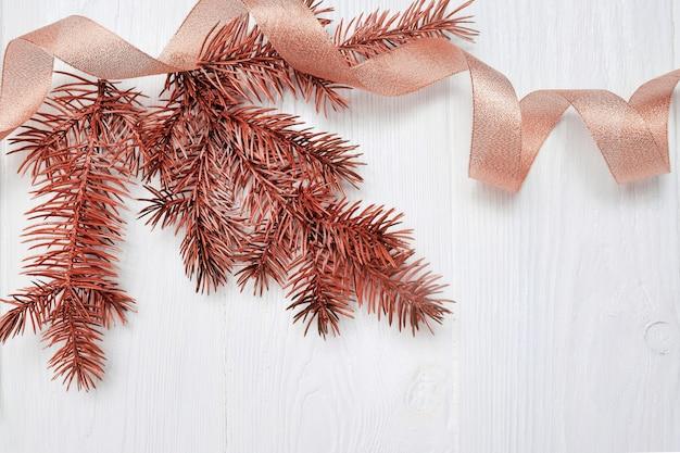 Maquette branche d'arbre de noël et ruban cadeau or, flatlay sur blanc