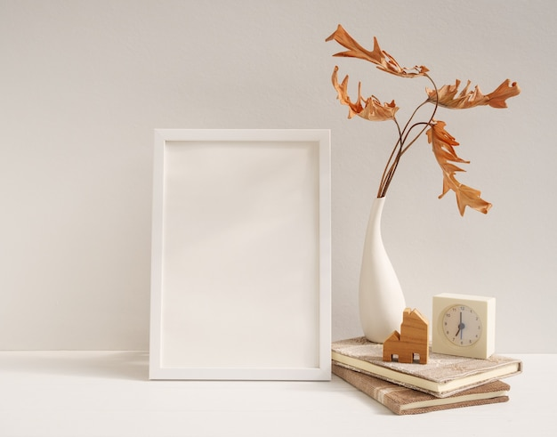 Maquette de cadre d'affiche en bois blanc, feuille séchée philodendron dans un vase horloge livres modèle de maison sur table beige