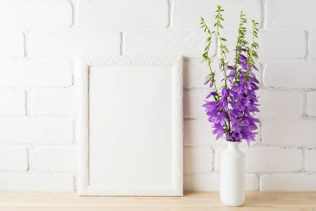 Maquette de cadre blanc avec bouquet de campanule violet près du mur de briques