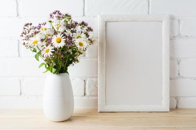 Maquette de cadre blanc avec bouquet de fleurs sauvages en fleurs près du mur de briques peintes