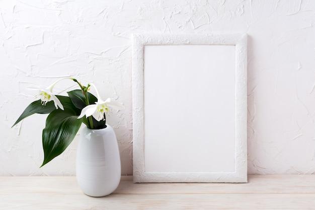 Maquette de cadre blanc avec fleur euxaris dans un vase