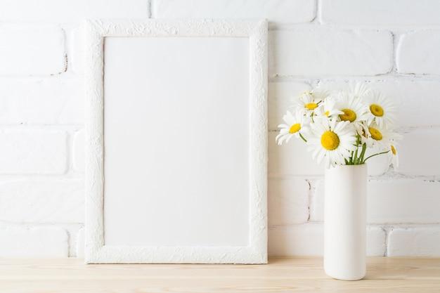 Maquette de cadre blanc avec fleur de marguerite près de mur de briques peintes