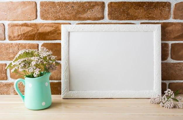 Maquette de cadre blanc fleurs rose crème dans un pichet à la menthe