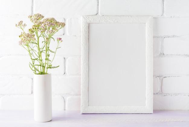 Maquette de cadre blanc avec des fleurs rose crème dans un vase cylindrique