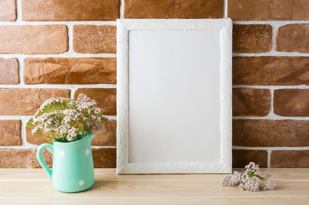 Maquette de cadre blanc avec des fleurs roses crème près des briques exposées