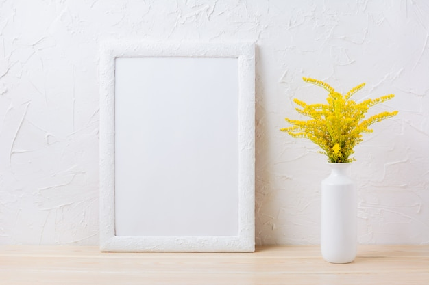 Maquette de cadre blanc avec de l'herbe à fleurs jaunes ornementales dans un vase