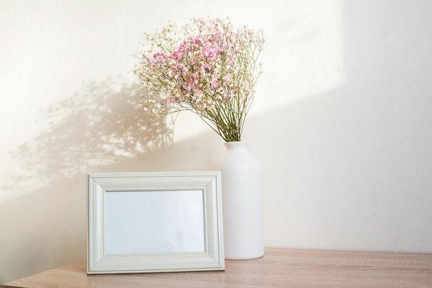 Maquette de cadre blanc horizontal sur banc en bois vintage, table. vase moderne en céramique blanche gypsophile. fond de mur blanc.