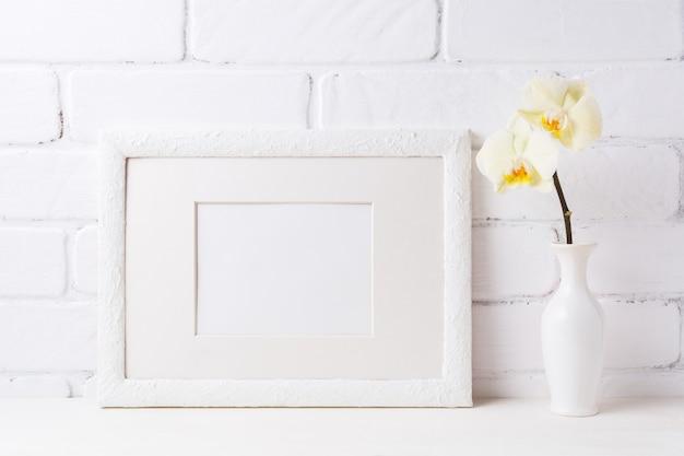 Maquette de cadre blanc avec orchidée jaune tendre dans un vase