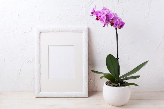 Maquette de cadre blanc avec orchidée pourpre en pot de fleur
