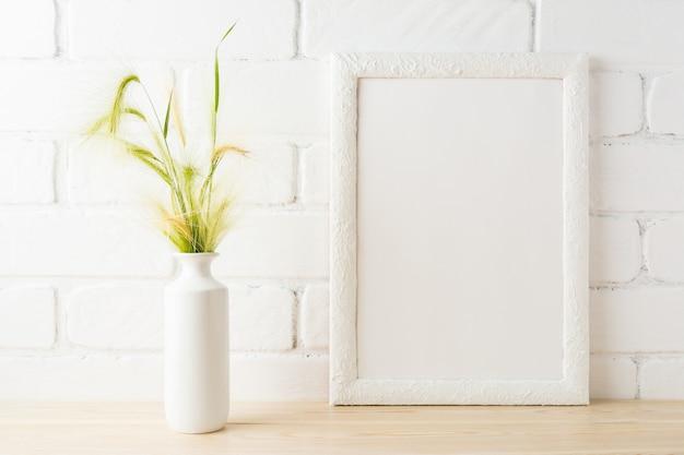 Maquette de cadre blanc avec des oreilles d'herbe sauvage jaune et verte