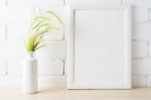 Maquette de cadre blanc avec des oreilles d'herbe sauvage près du mur de briques peintes