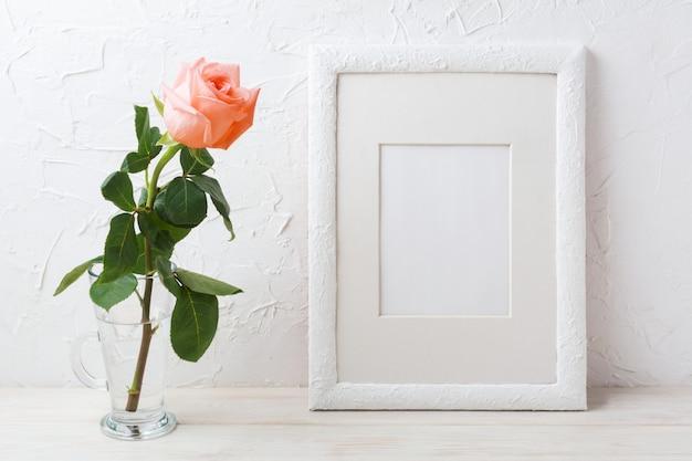 Maquette de cadre blanc avec rose rose crème dans un vase en verre