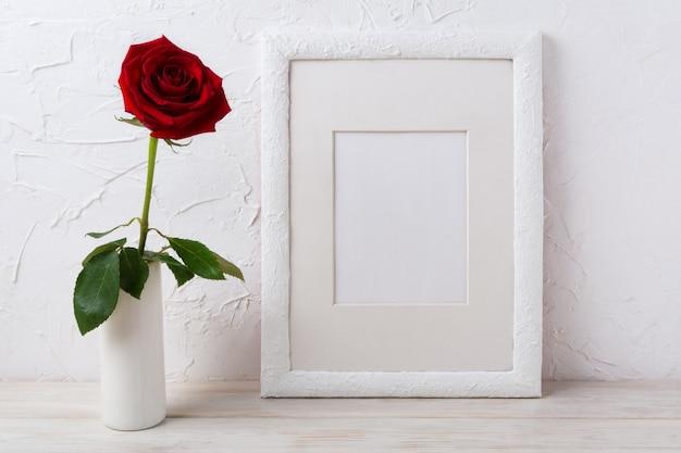 Maquette de cadre blanc avec rose rouge foncé dans un vase