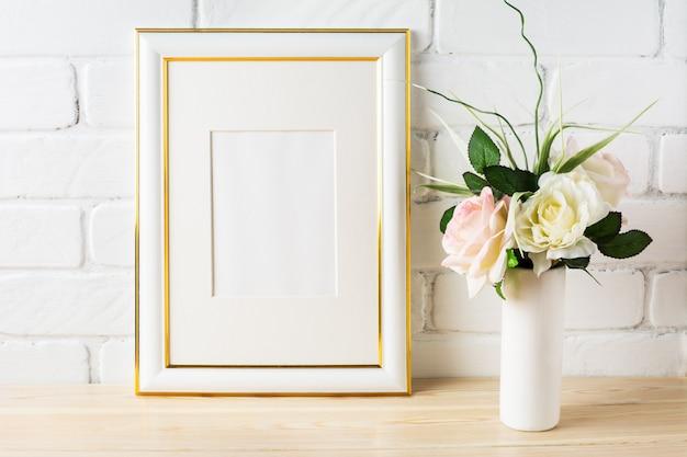Maquette cadre blanc avec roses roses pâles dans un vase
