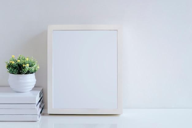 Maquette un cadre en bois blanc, des livres et une plante d'intérieur sur un tableau blanc