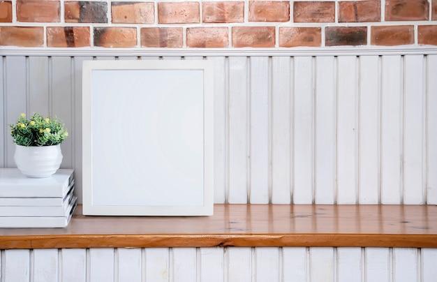 Maquette un cadre en bois blanc sur une table en bois avec mur de briques