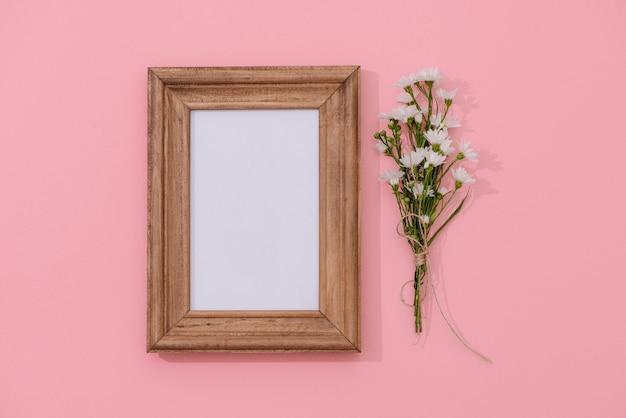 Maquette de cadre en bois avec des fleurs tombées en arrière-plan