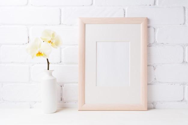 Maquette de cadre en bois avec orchidée jaune tendre dans un vase