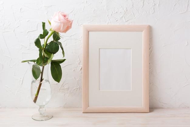 Maquette de cadre en bois avec rose dans un vase en verre exquis
