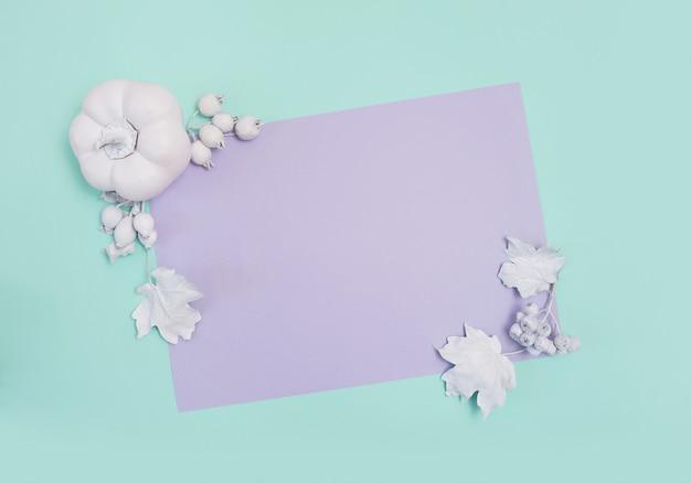 Maquette de cadre avec citrouille, baies et feuilles sur carte turquoise et violette