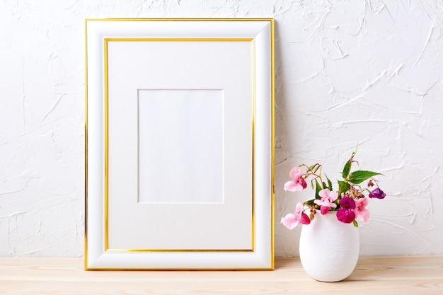 Maquette de cadre décoré d'or avec bouquet de fleurs en pot de fleurs