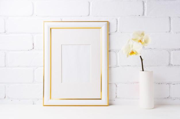 Maquette de cadre décorée en or avec orchidée jaune tendre dans un vase