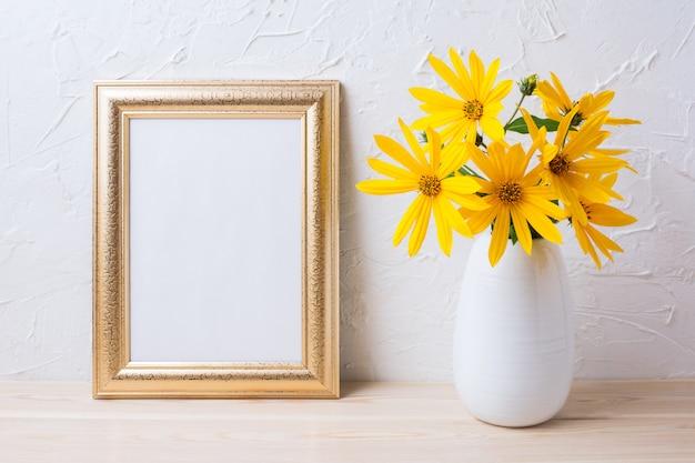 Maquette de cadre doré avec des fleurs de rosarin jaune dans un vase