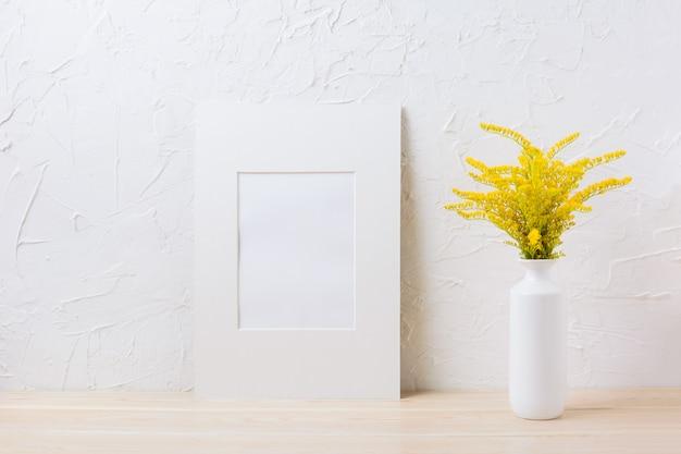 Maquette de cadre mat blanc avec de l'herbe à fleurs jaunes ornementales dans un vase