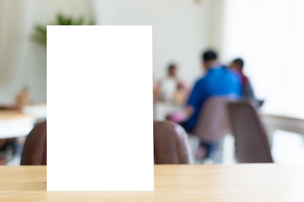 Maquette cadre de menu modèle vierge sur la table en bois dans le restaurant avec l'arrière-plan flou
