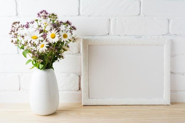 Maquette de cadre de paysage blanc avec bouquet de fleurs sauvages en fleurs dans un vase