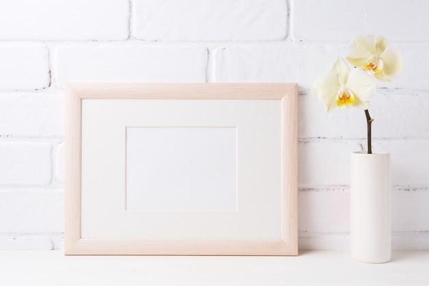 Maquette de cadre de paysage en bois avec orchidée jaune tendre dans un vase