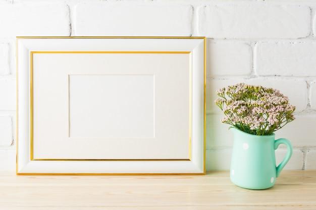 Maquette de cadre de paysage décoré d'or fleurs roses douces dans un pichet