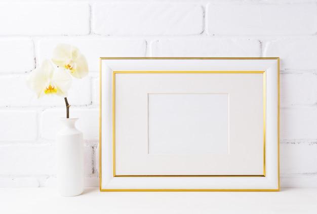 Maquette de cadre paysage décorée d'or avec une orchidée jaune tendre dans un vase