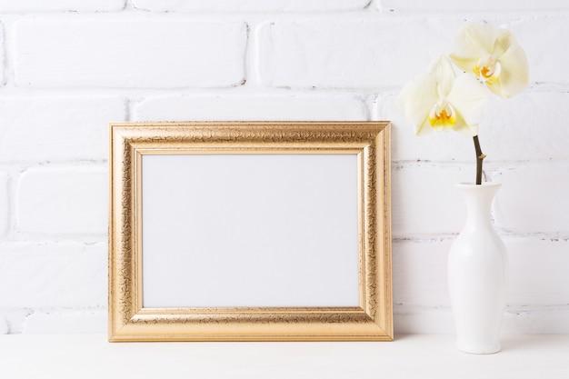 Maquette de cadre de paysage doré avec orchidée jaune tendre dans un vase