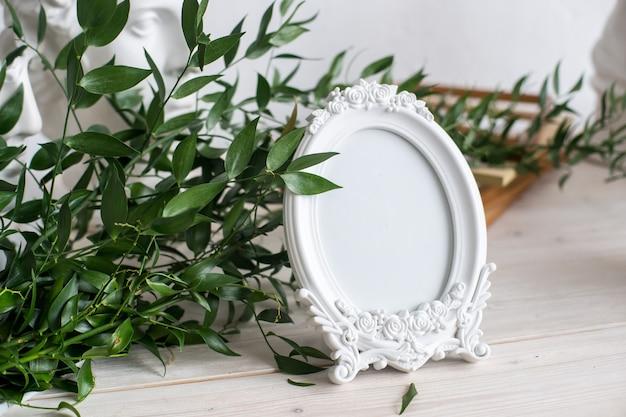 Maquette de cadre photo blanc portrait sur table en bois vase en céramique moderne avec fond de mur blanc gypsophile intérieur scandinave