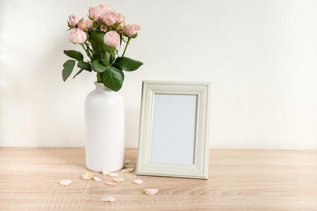 Maquette de cadre photo blanc portrait sur table en bois vase en céramique moderne avec des roses fond de mur blanc intérieur scandinave