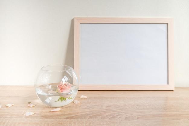 Maquette de cadre photo blanc portrait sur table en bois vase en verre moderne avec des roses fond de mur blanc intérieur scandinave