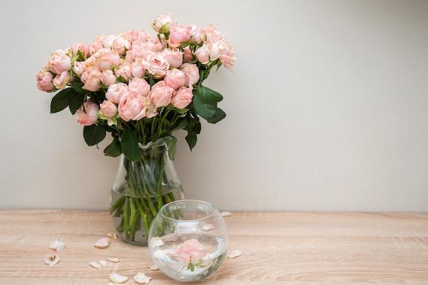 Maquette de cadre photo blanc portrait sur table en bois vase en verre moderne avec des roses mur blanc intérieur scandinave