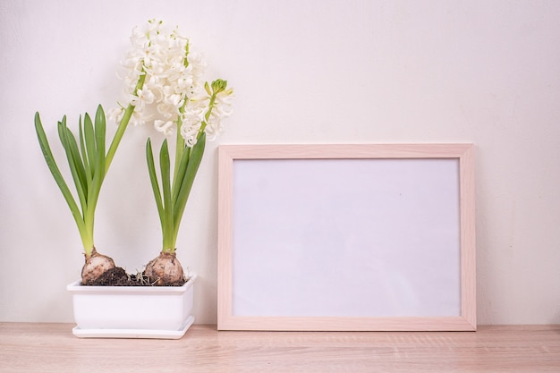 Maquette de cadre photo blanc portrait sur table en bois.