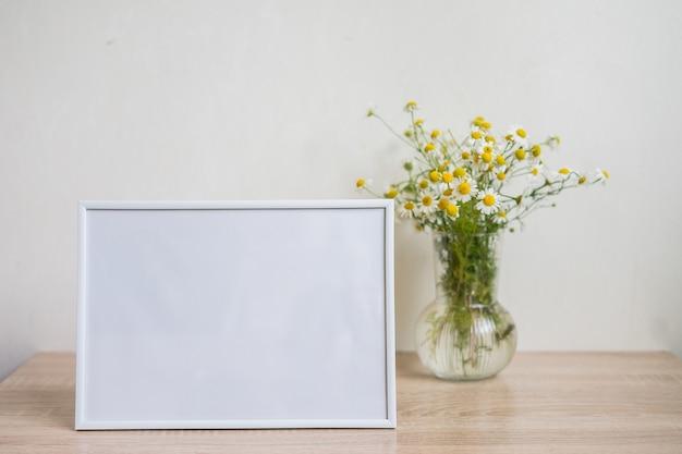 Maquette de cadre photo blanc portrait sur vase en verre de table en bois avec camomille
