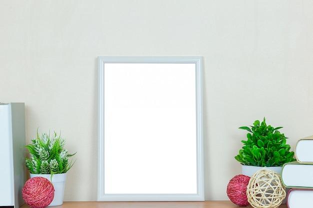 Maquette cadre photo blanc sur table en bois.