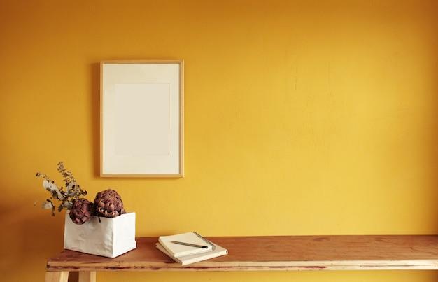 Maquette de cadre photo en bois. pot de fleurs sur une pile de livres sur une vieille étagère en bois. composition sur une surface de mur jaune