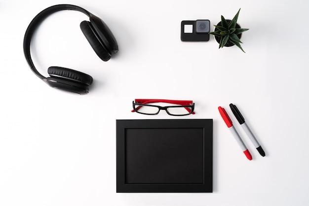 Maquette, cadre photo, caméra d'action, casque, lunettes, stylo et cactus, objet rouge et noir sur fond blanc