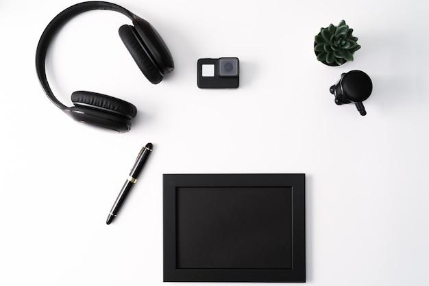 Maquette, cadre photo, caméra d'action, casque, stylo et cactus, objet noir sur fond blanc