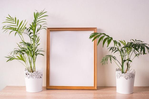Maquette de cadre photo portrait broun sur table en bois. fond de mur blanc. intérieur scandinave.