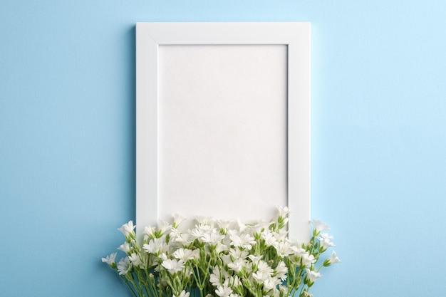 Maquette de cadre photo vide blanc avec des fleurs de mouron des oreilles de souris